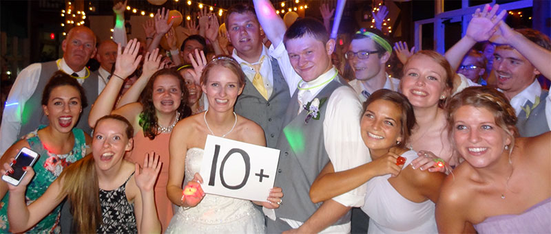 Bride holding a '10+' sign with groom and very happy crowd, another successful Susie Show wedding!